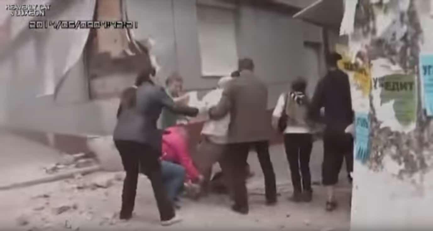 """Наслідки випадкового пострілу цивільного з покинутої БМП №240: видно пошкодження будівлі """"Дельта-банку"""" і поранений уламками перехожий, якому надають допомогу."""